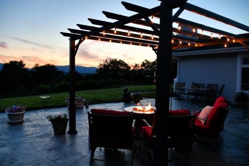 Backyard during the night with an outdoor fireplace going and patio furniture surrounding it