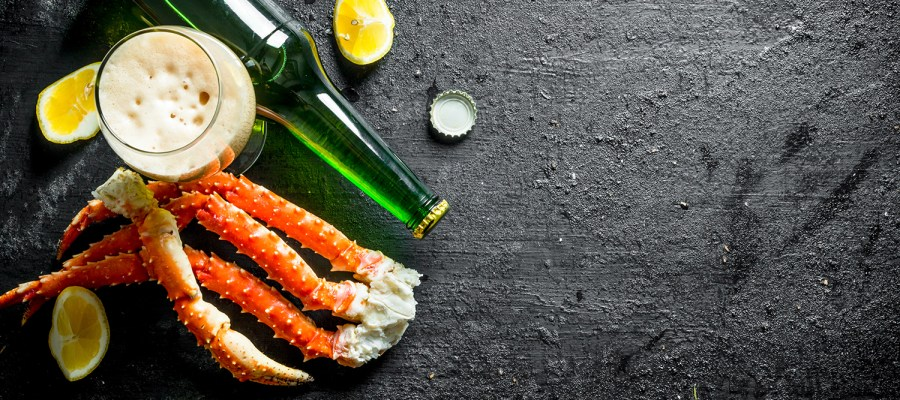 Crab legs on black rustic surface with lemon slices and foaming beer