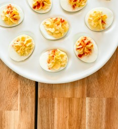Deviled eggs with spices on top resting on white platter on wooden table