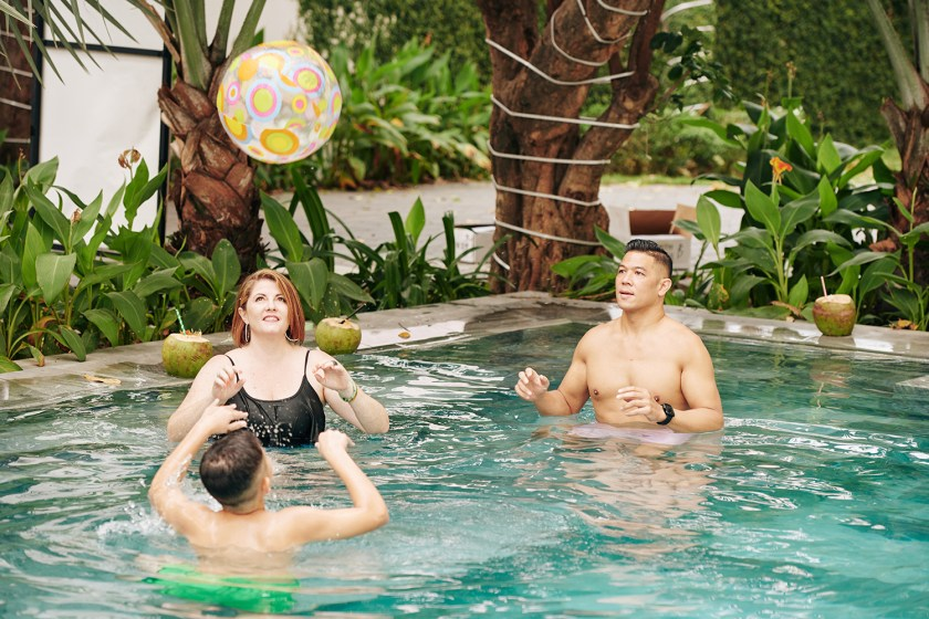 A family of three playing volleyball with an inflatable ball in a swimming pool