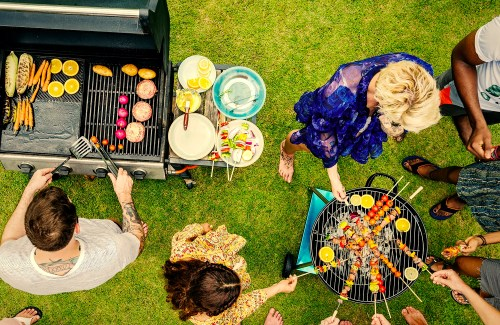 People gathered around grills in backyard for a barbecue dinner at a summer party