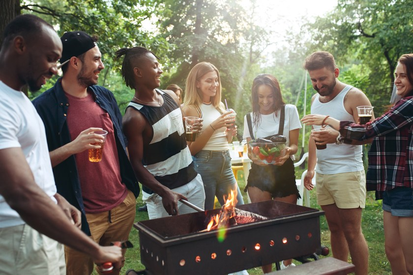 Group of friends eating food in the backyard around an open flame while talking and laughing