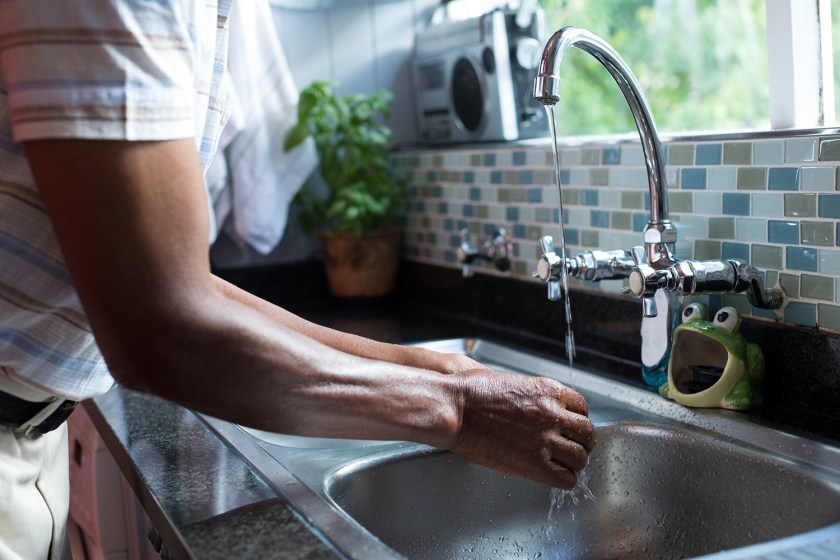Man washing his hands at sink by window