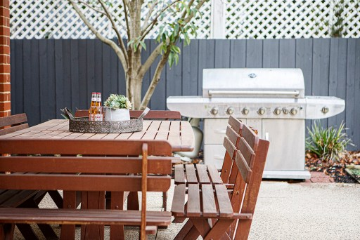 Outdoor kitchen with luxury grill in the background and outdoor seating in the foreground