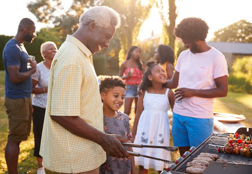 Grandpa and grandson near the grill at a family party, while the grandpa uses the tongs to turn the food.