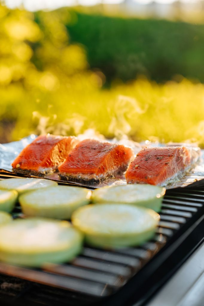 Salmon and veggies cooking on grill outside