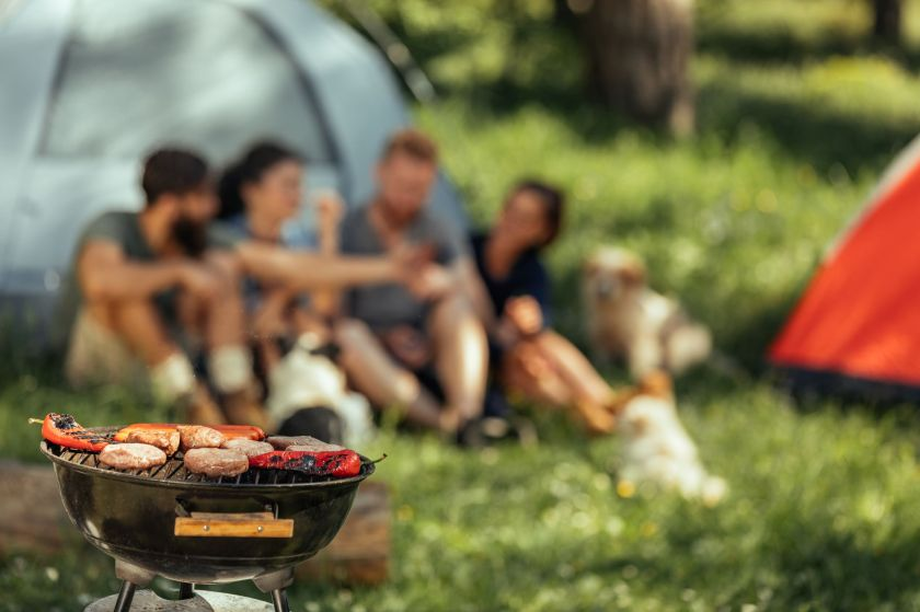 Small grill cooking food while friends in the background enjoy themselves chatting near their tents