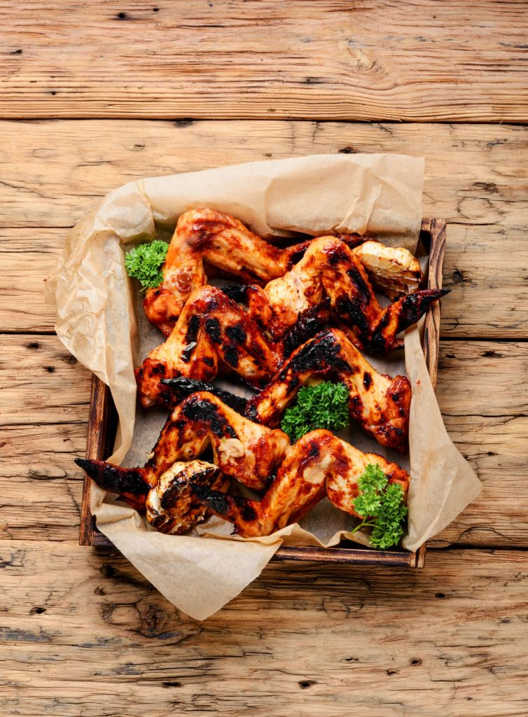 Grilled chicken in a basket with some butcher paper in it and garnish on a table.
