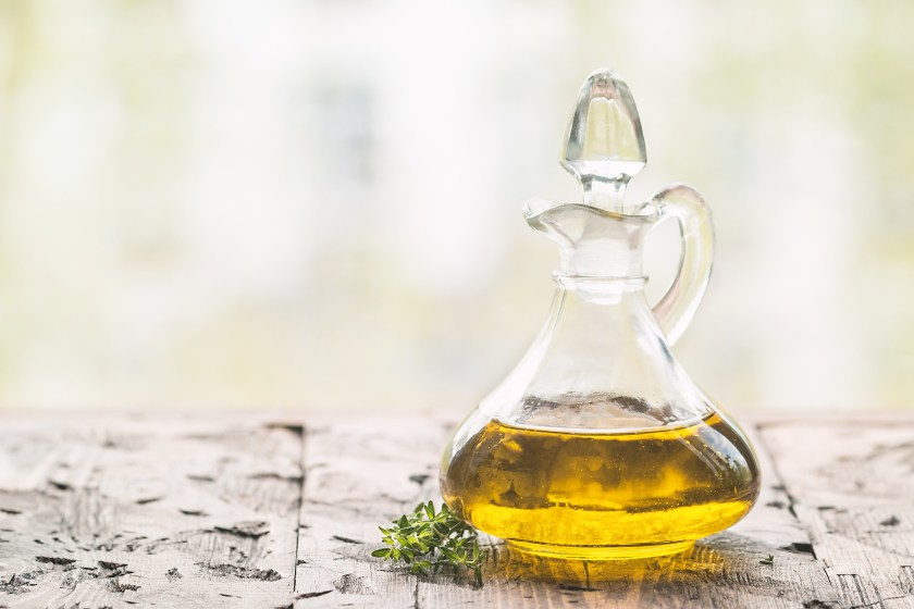 Olive oil in a decanter on a wooden surface