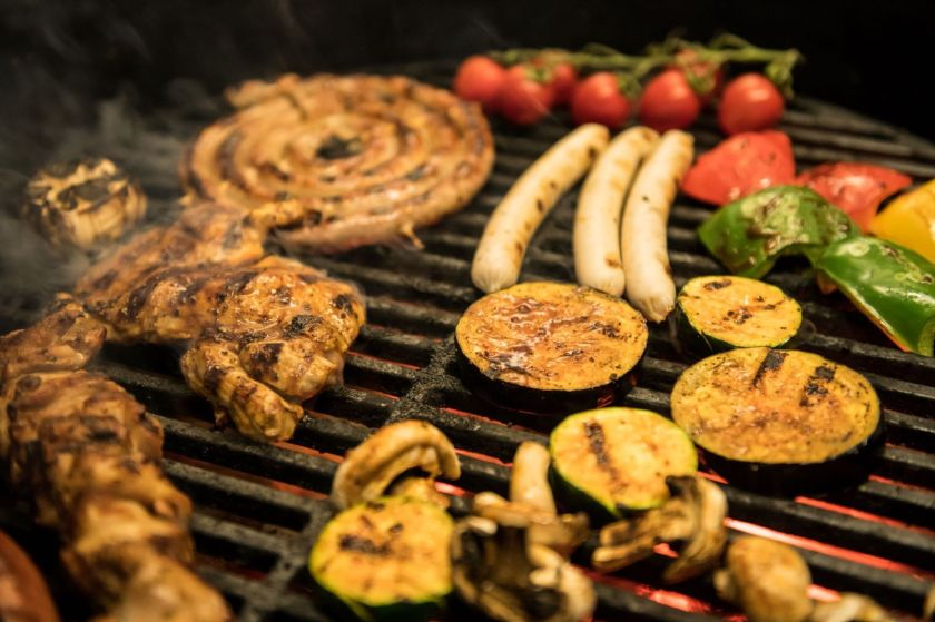 Veggies and meat scattered on grill and all charred after being cooked over flames
