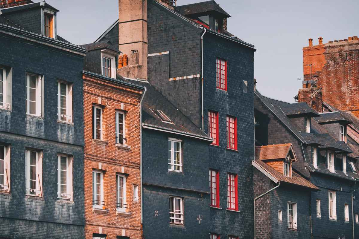 facades of historical brick buildings under cloudy sky in town