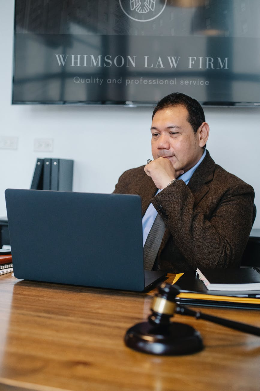thoughtful asian lawyer browsing laptop in law office