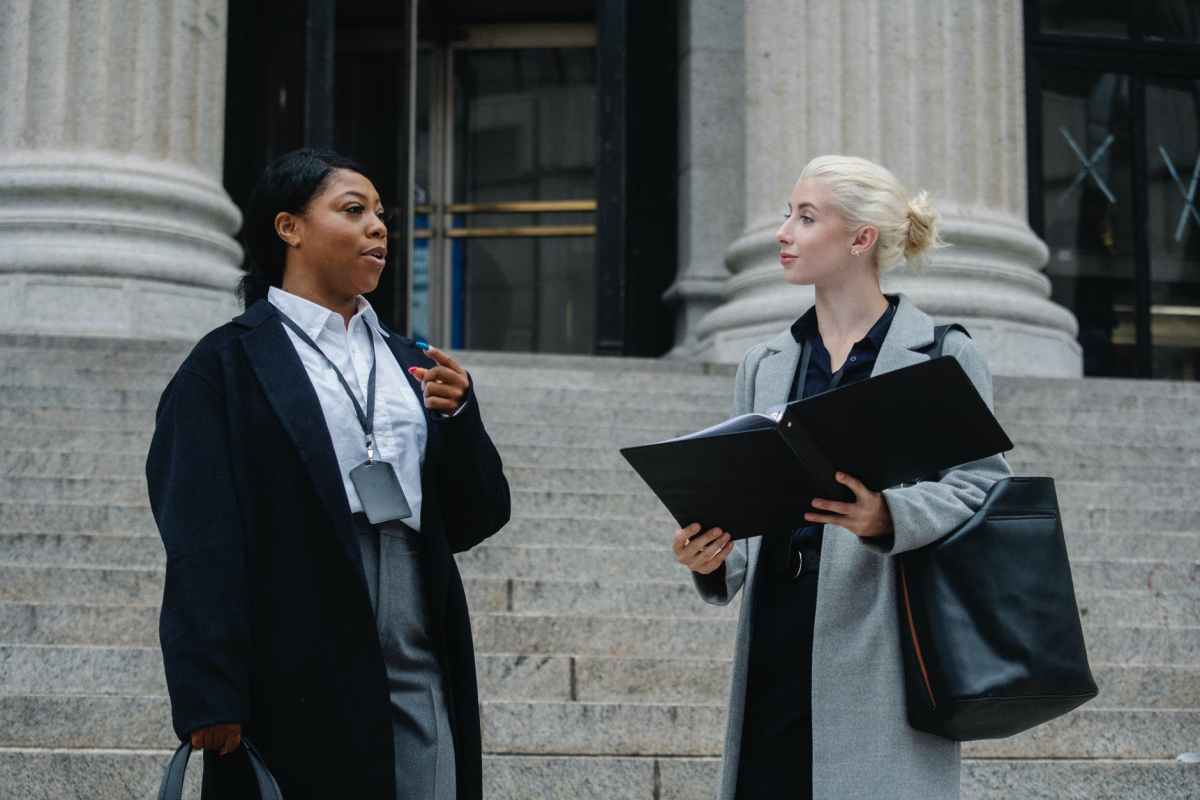 elegant diverse female business partners with documents talking on street