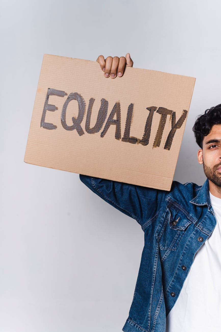 man in blue denim jacket holding brown cardboard with equality text
