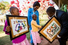 Dr. Peter Kumpalume is presented with paintings by children during the dedication. ( Photo by Smiley N. Pool / © 2016 )