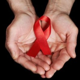 closeup of hads holding AIDS awareness ribbon