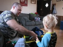 My husband helping our son open his pretend weed eater toy