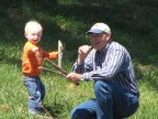 My son and my dad playing with sticks in the field by our house.