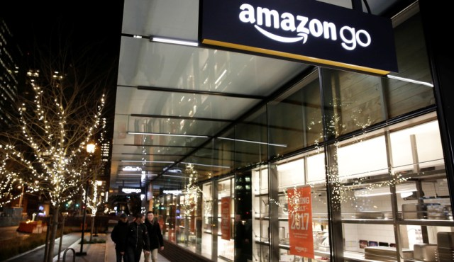 People walk by the Amazon Go brick-and-mortar grocery store without lines or checkout counters, in Seattle Washington, U.S. December 5, 2016. REUTERS/Jason Redmond - RTSUU23