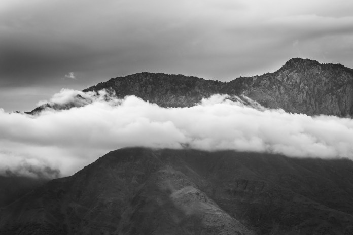 Low hanging white clouds in front of a mountain with dark moody