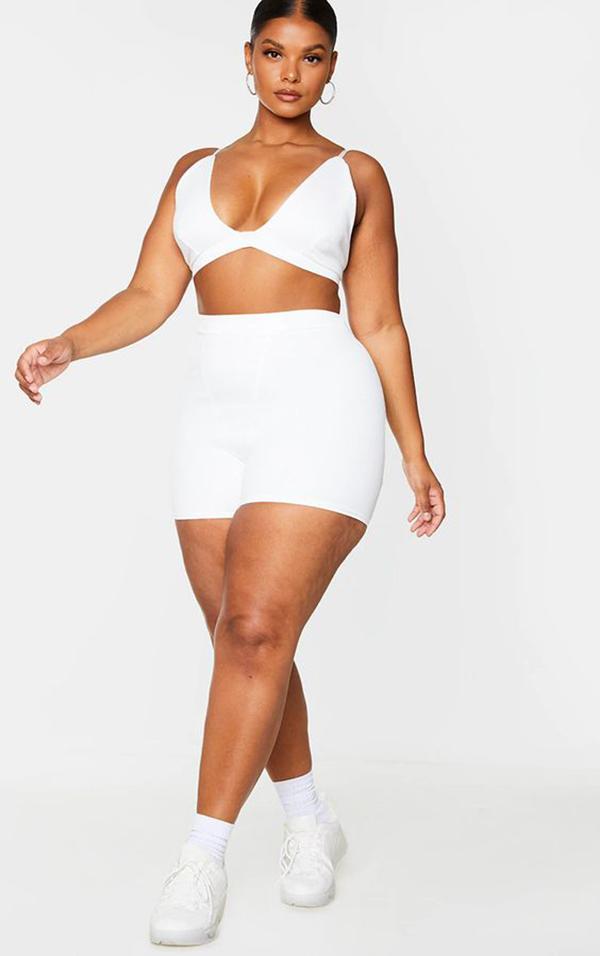 A plus-size model wearing white bike shorts.