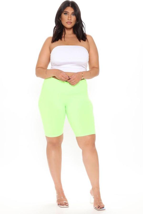 A plus-size model wearing neon yellow bike shorts.