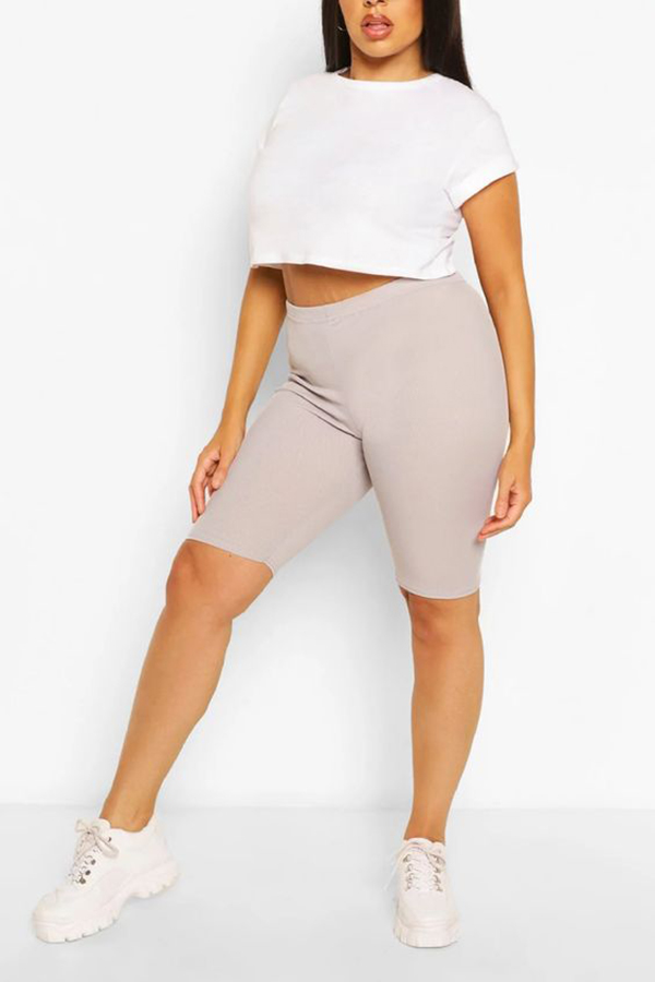 A plus-size model wearing taupe bike shorts.