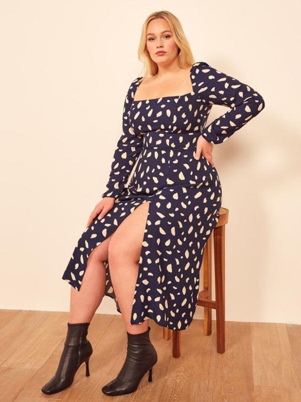 Woman wearing a navy polka dot cocktail dress.
