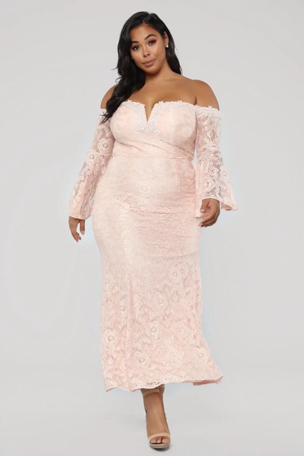 Woman wearing a light pink cocktail dress.