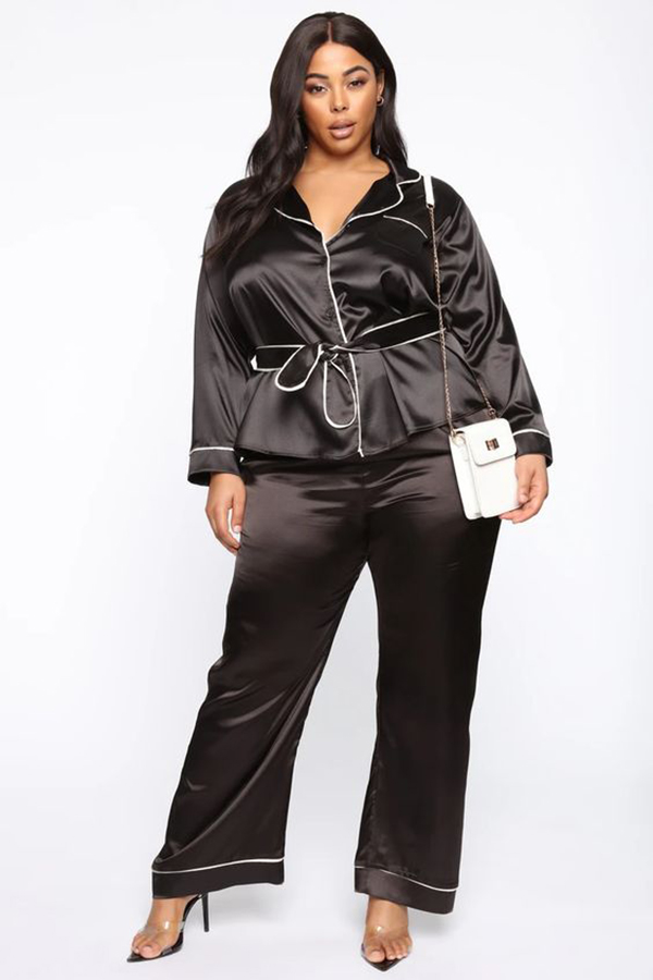 A plus-size model wearing a black silky matching set.