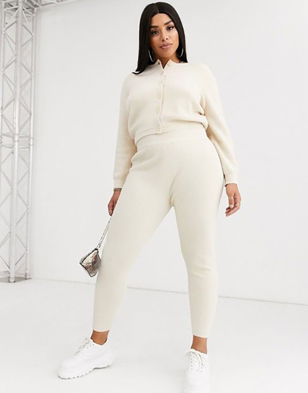 A plus-size model wearing a white matching set.