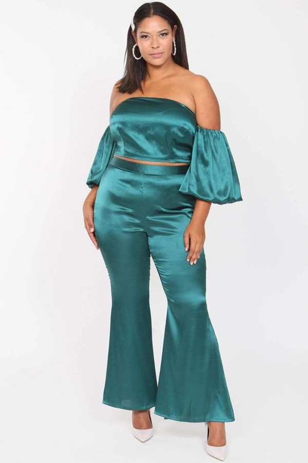 A plus-size model wearing a teal matching set.