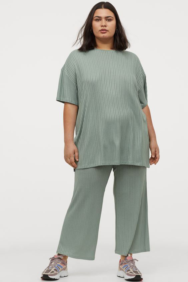 A plus-size model wearing a gray-green matching set.