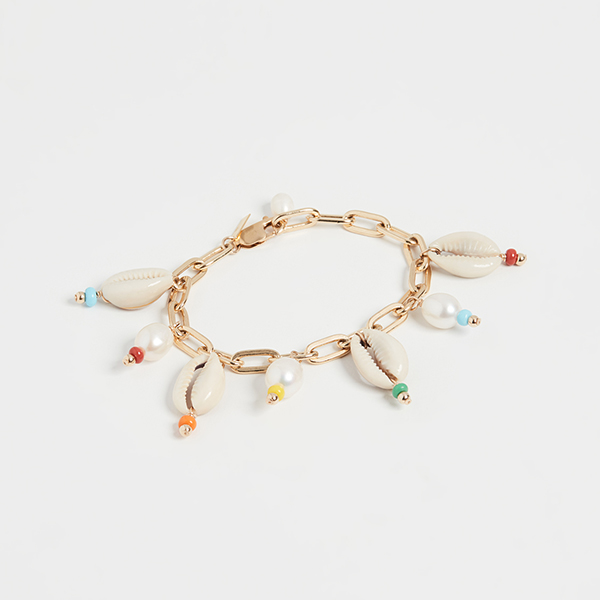 A gold chain necklace lined with cowrie shells.