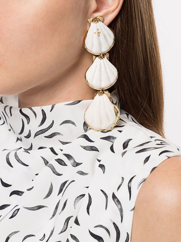 A model wearing a drop earring with three scallop shells on it.