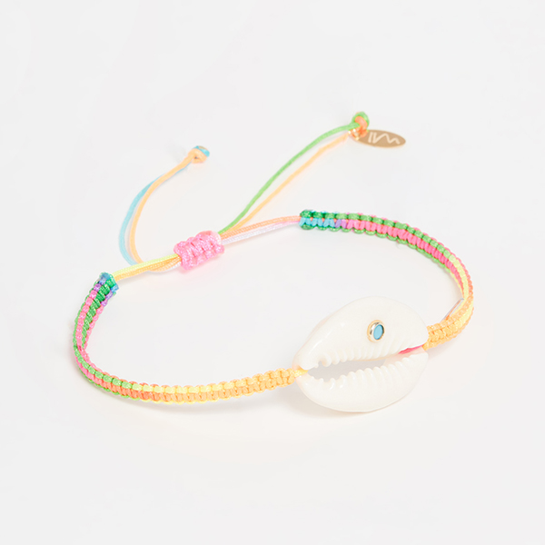 A colorful woven bracelet with a cowrie shell on it.
