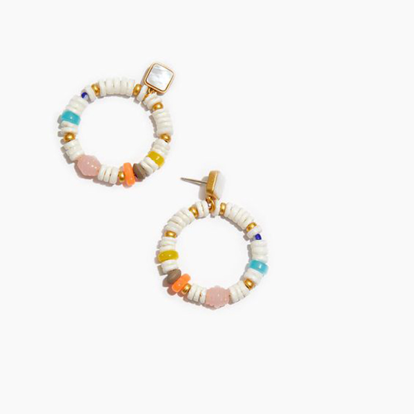 A pair of drop hoop earrings covered in rounded puka shells.