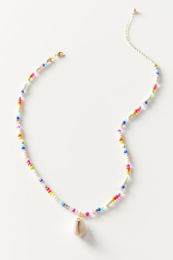 A rainbow beaded necklace with a cowrie shell on it.