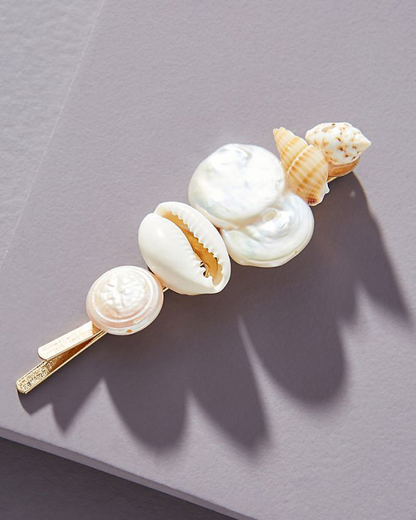 A hair barrette with a collection of shells on it.