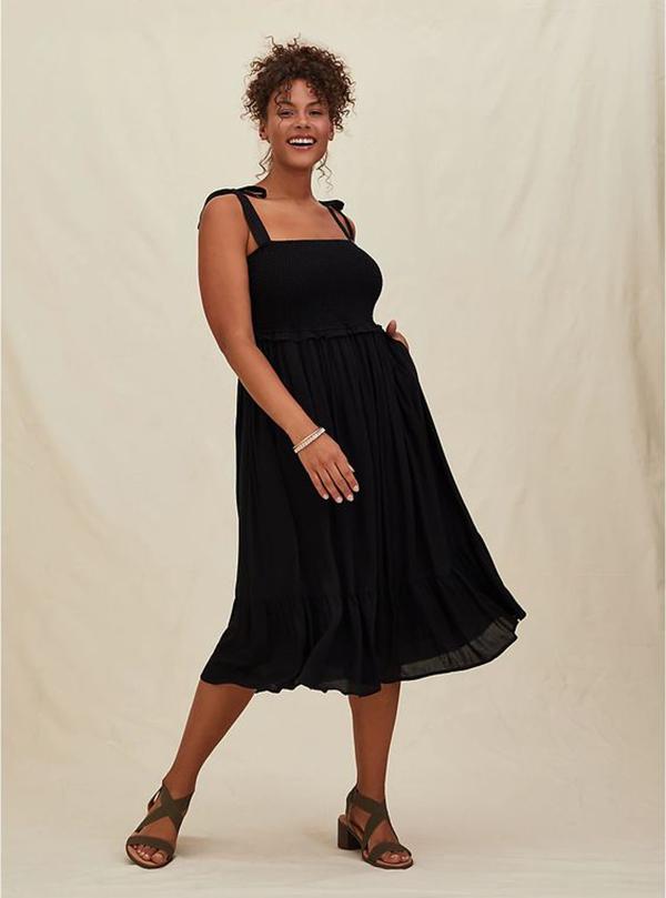 A plus-size model wearing a black dress.