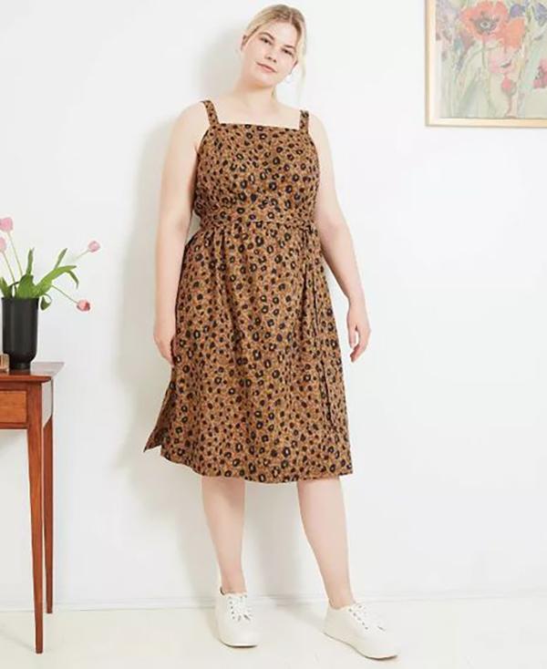 A plus-size model wearing an animal print dress.