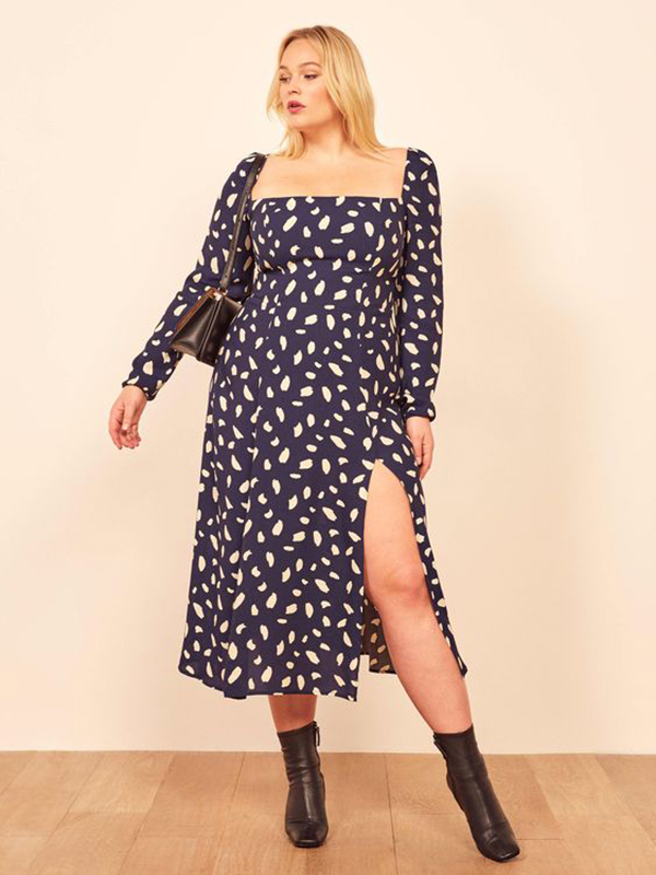 A plus-size model wearing a printed blue dress.