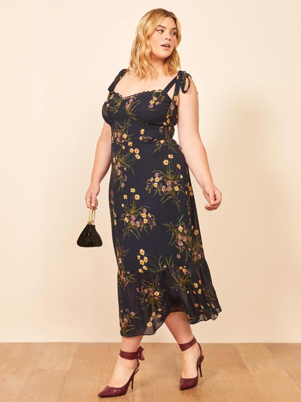 A plus-size model wearing a navy floral dress.