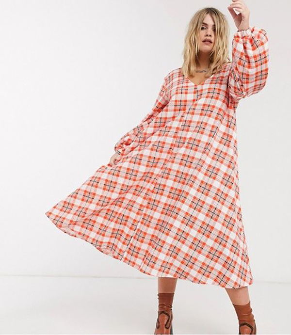 A plus-size model wearing a pink plaid dress.