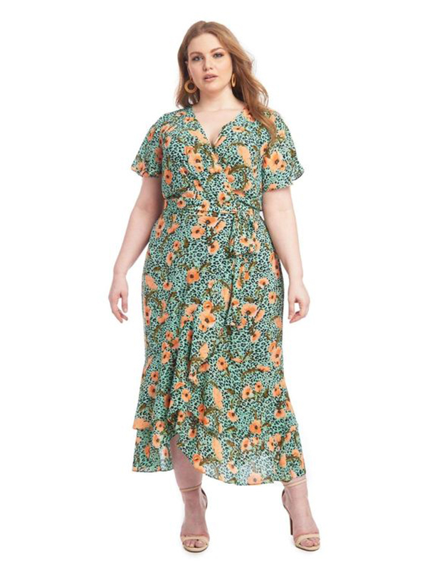 A plus-size model wearing a green floral dress.