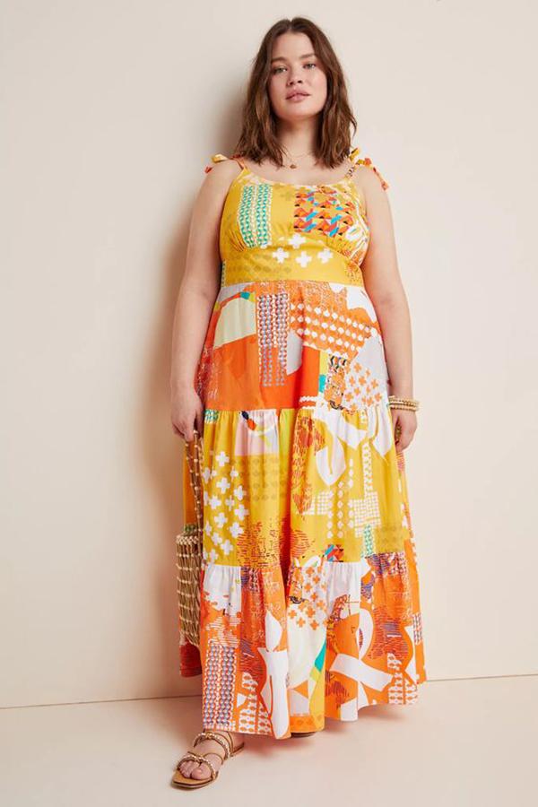 A plus-size model wearing an orange printed maxi dress.