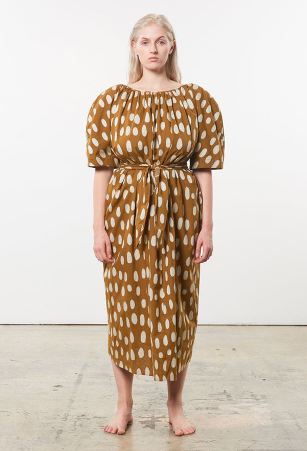 A plus-size model wearing a printed brown dress.
