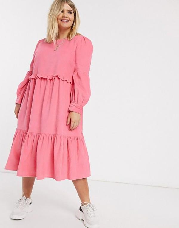A plus-size model wearing a pink midi dress.