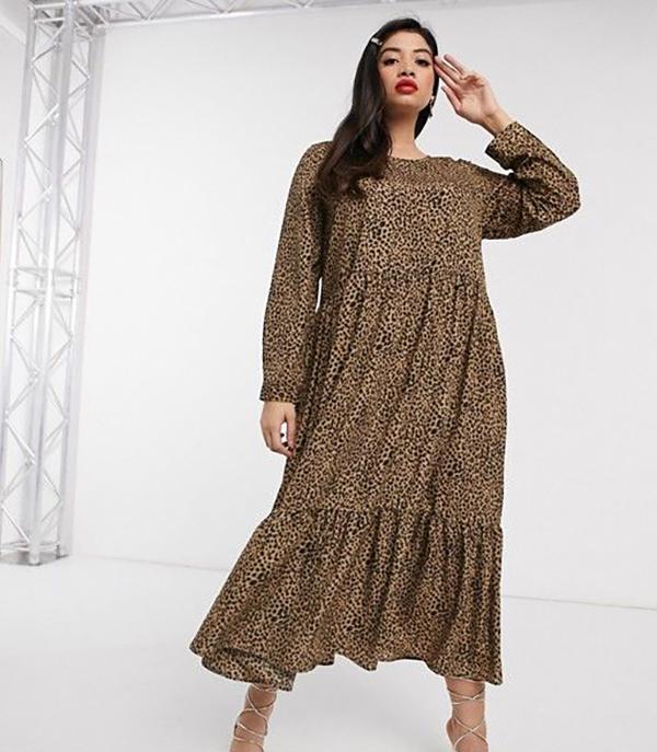 A plus-size model wearing an animal print midi dress.