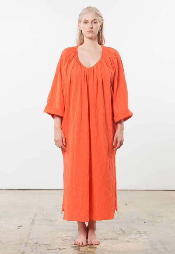A plus-size model wearing an orange maxi dress.